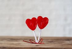 Two red heart shaped lollipops as metaphor of love, togetherness and Valentines day concept royalty free stock images