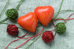 Two red heart shapes and four cotton clew balls Stock Images