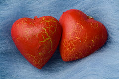 Two red heart shapes on sky blue wool Stock Image