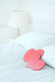 Two red heart symbols on white bed Royalty Free Stock Images