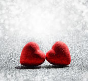 Two red Hearts on abstract light glitter background Stock Photos