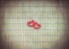 Two red hearts on bamboo napkin royalty free stock photography