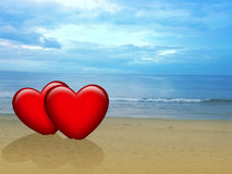 Two red hearts on the beach Stock Images