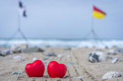 Two red hearts on the beach with surf flags in the background Royalty Free Stock Photos