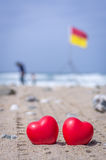 Two red hearts on the beach with surf flags in the background Stock Photo