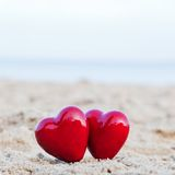 Two red hearts on the beach symbolizing love Stock Photos