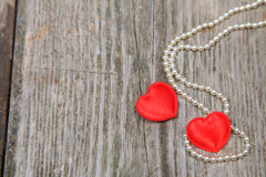 Two red hearts and beads Stock Photo