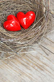 Two red hearts in a bird nest on wooden board Stock Photo