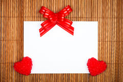 Two red hearts and bow with paper card Royalty Free Stock Photos