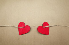 Two red hearts on brown paper Royalty Free Stock Image
