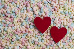 Two red hearts on colorful mini marshmallows background Royalty Free Stock Image