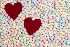 Two red hearts on colorful mini marshmallows background Royalty Free Stock Photo