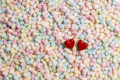 Two red hearts on colorful mini marshmallows background Stock Photography