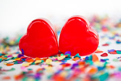 Two red hearts with confetti Stock Images