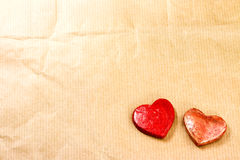 Two red hearts on crumpled paper Stock Photos