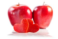 Two red hearts are cut out from apple, two red apples on a backg. Round. White background, close up, selective focus Royalty Free Stock Image