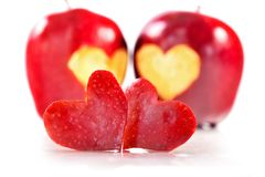 Two red hearts are cut out from apple, two red apples on a backg. Round. White background, close up, selective focus Stock Photo