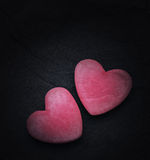 Two red hearts on a dark background, soft focus. Romantic card. Stock Images