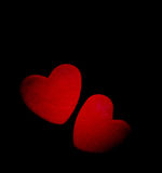 Two red hearts on a dark background, soft focus. Romantic card. Royalty Free Stock Photo