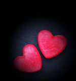 Two red hearts on a dark background, soft focus. Romantic card. Stock Photos