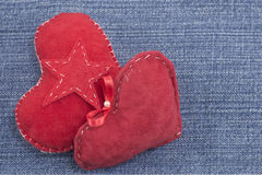 Two red hearts on denim background Royalty Free Stock Images