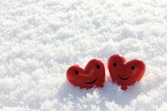 Two red hearts with face in snow - happy Stock Image