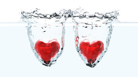 Two red hearts falling into water Royalty Free Stock Image