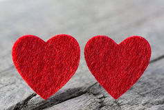 Two red hearts of felt on a wooden old shabby background. Stock Photo