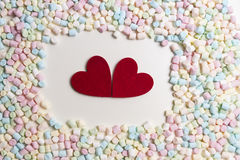 Two red hearts in the frame of colorful mini marshmallows as background Stock Photography