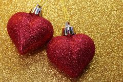 Two red hearts glitter on golden texture shining Stock Image