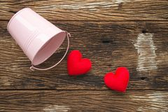 Two red hearts go out pink tank on old wooden background - valen Royalty Free Stock Photo