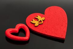 Two red hearts with gold doves on a black glass background royalty free stock images