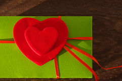 Two red hearts on a green background with a red tape Stock Photo