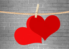 Two red hearts hang on clothespin over grey brick wall Royalty Free Stock Image