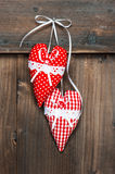 Two red hearts hanging over wooden background Royalty Free Stock Image