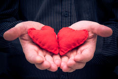 Two red hearts held male hands Royalty Free Stock Images