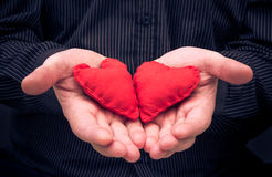 Two red hearts held male hands Stock Images