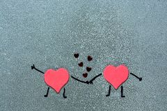 Two red hearts holding hands on a gray background. Hearts with painted hands and feet. Loving hearts Royalty Free Stock Photos