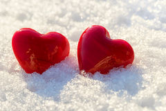 Two red hearts on ice wet snow, selective focus Stock Photos