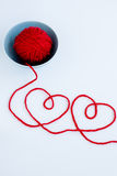 Two red hearts made from yarn, yarn ball of red and plate Royalty Free Stock Photo