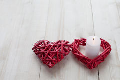 Two red hearts in one is a candle lit on wooden background, Valentine`s day, the holiday of love Royalty Free Stock Images