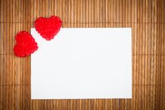 Two red hearts with paper card Stock Photos