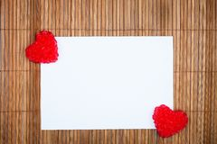 Two red hearts with paper card Royalty Free Stock Photography