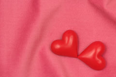 Two red hearts on a pink fabric Royalty Free Stock Images