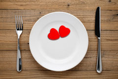 Two red hearts on plate. On wooden background Stock Photography
