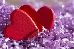 Two red hearts in purple paper tinsel. Postcard or background on Valentine`s Day Stock Photo