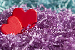 Two red hearts in purple and turquoise paper tinsel. Postcard or background on Valentine`s Day Royalty Free Stock Photos