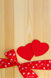 Two red hearts with a red tape and a bow Stock Images