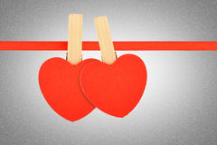 Two red hearts at ribbon over grayscale noise Stock Images
