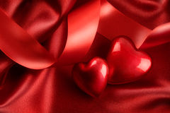 Two red hearts with ribbon on satin Stock Photo
